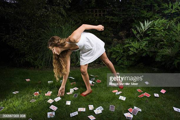 Girl (10-11) picking up 'ace of diamonds' card from cards on grass