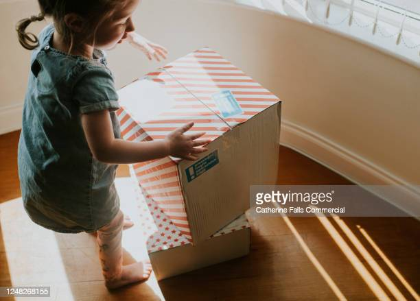 girl picking up cardboard boxes in sunstreams - buying stock pictures, royalty-free photos & images