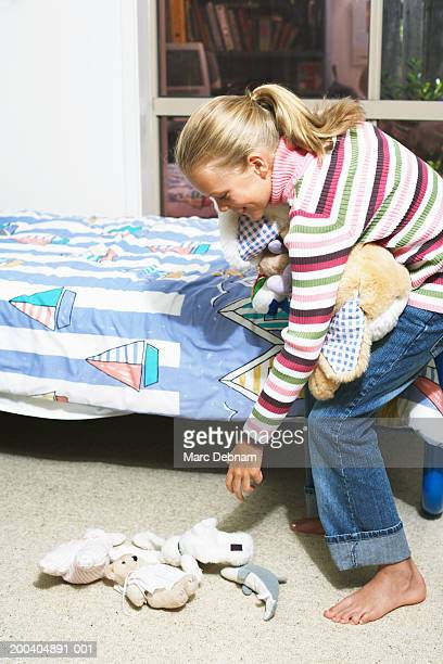Girl (10-12) picking up cuddly toys from bedroom floor, side view