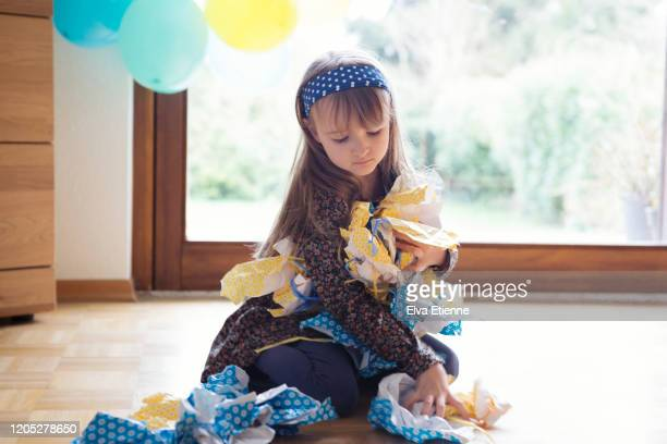 girl (6-7) picking up discarded wrapping paper after a birthday celebration - messy house after party stock pictures, royalty-free photos & images