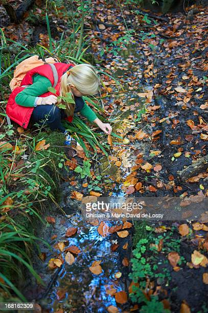Girl piking up leaves from a stream