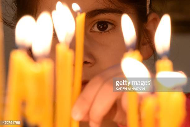 A girl places a candle during a religious service at the cathedral in Etchmiadzin outside Yerevan on April 23 ahead of the canonization ceremony for...