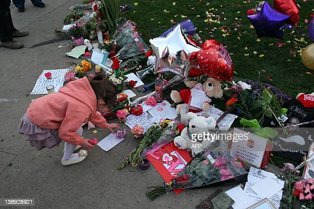 A girl places a flower at a makeshift memorial to Grammywinning pop legend and actress Whitney Houston near the Beverly Hilton Hotel on February 12...