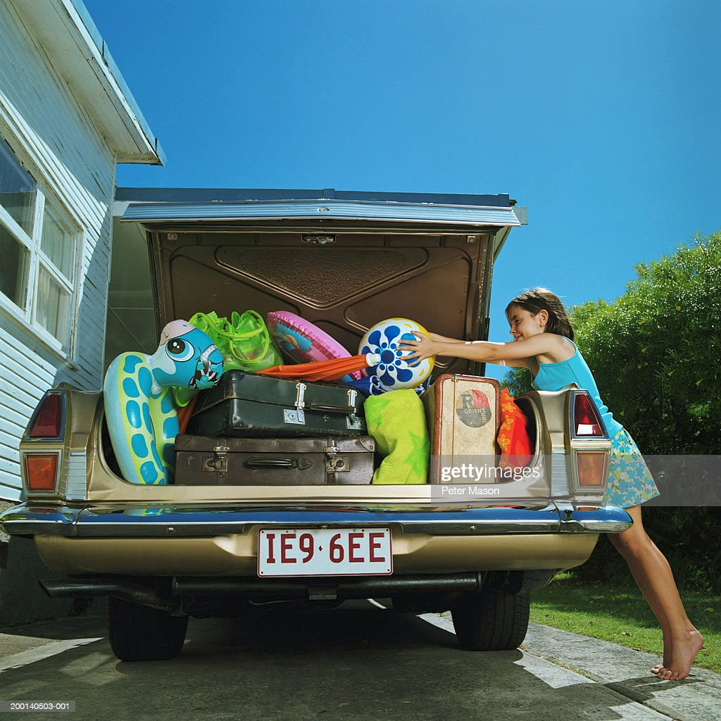 Girl (6-8) placing ball in heavilly loaded car boot : Stock Photo