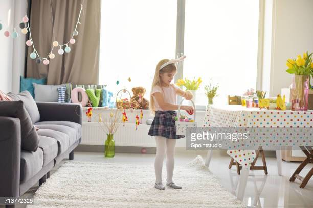 girl placing easter eggs into basket in living room - little girls in pantyhose stock pictures, royalty-free photos & images