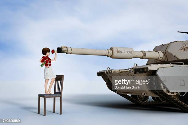 girl placing flowers in gun barrel of tank - armored tank stock photos and pictures