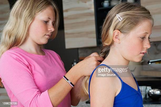 Girl plaiting friends hair