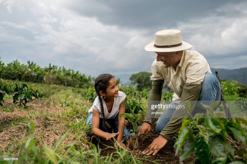 Girl planting a tree with her father at the farm : Stock Photo