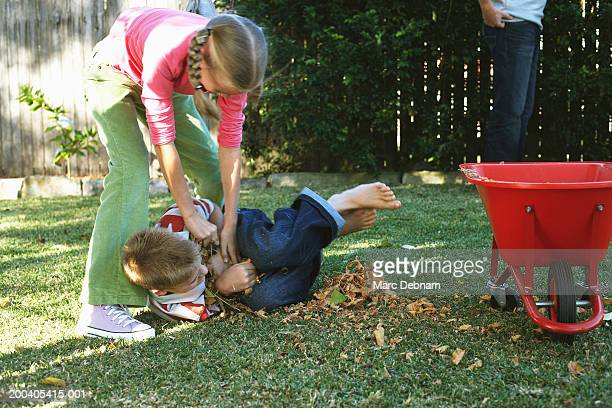Girl (10-12) play fighting with twin brother in garden