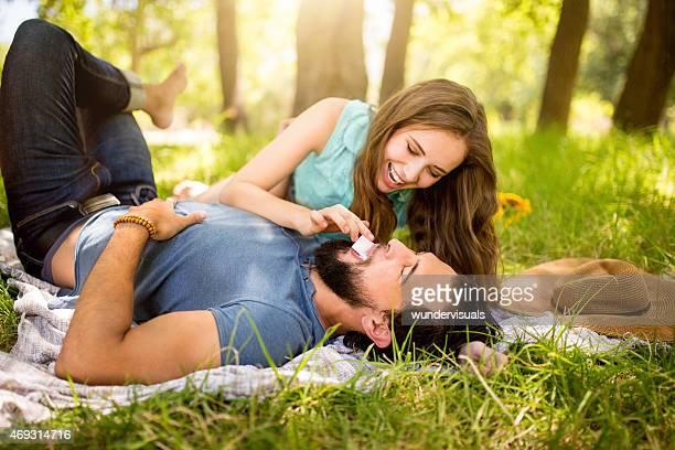 Girl playfully feeding her boyfriend chocolate in a park
