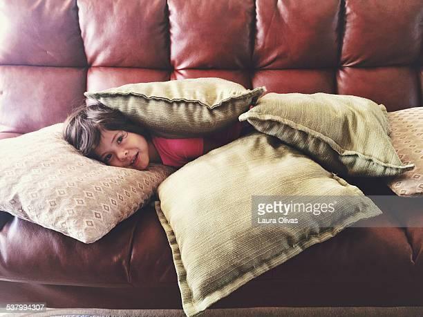 Girl Playfully Hiding Underneath Pillows