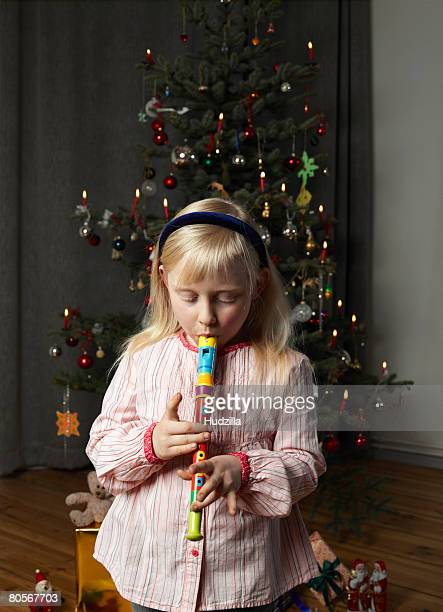 A girl playing a recorder in front of a Christmas tree