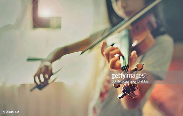Girl playing a violin in front of a window