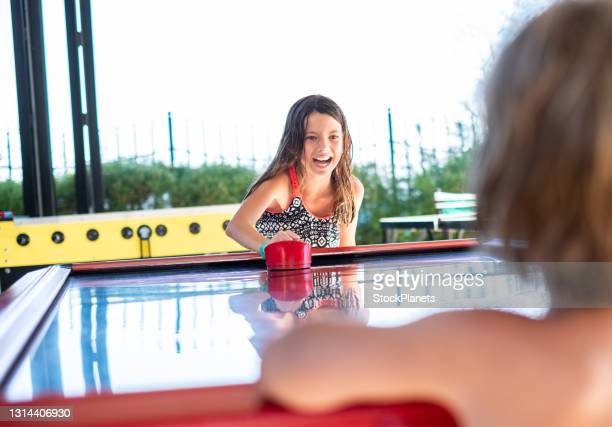 girl playing air hockey at the summer vacation - shooting at goal stock pictures, royalty-free photos & images