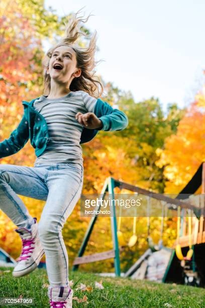 girl playing and jumping in garden - heshphoto stock pictures, royalty-free photos & images