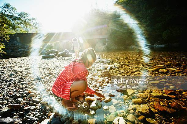 Girl playing at river edge on summer afternoon