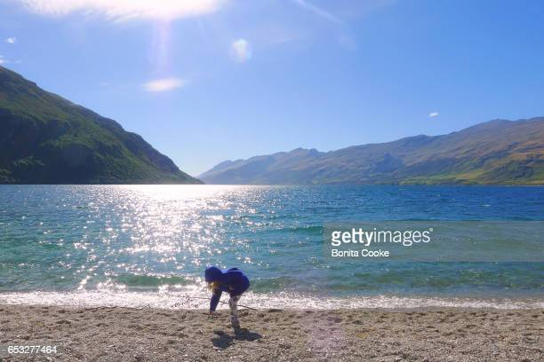 Girl playing at the lake shore at Kingston, Lake Wakatipu, Queenstown