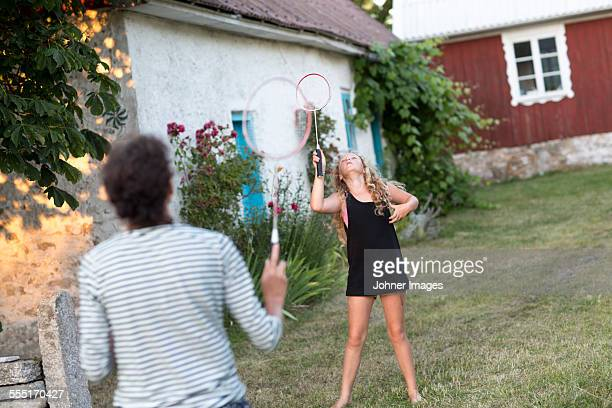 Girl playing badminton with mother