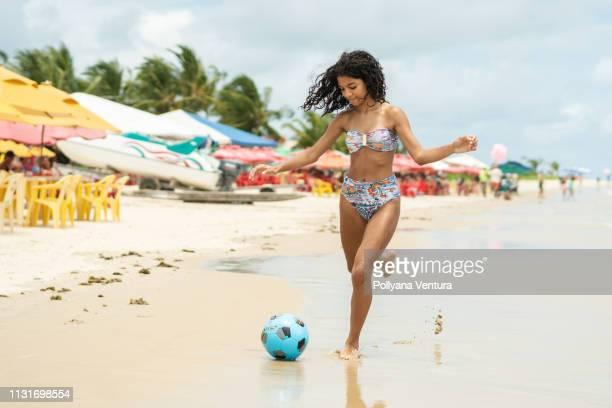 ビーチでボールを再生する女の子 - ビーチサッカー ストックフォトと画像