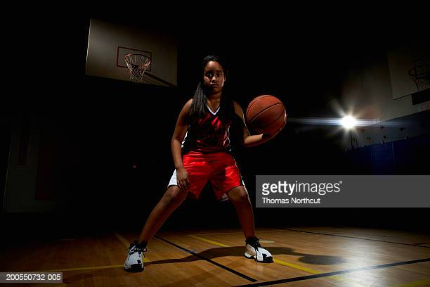 Girl (7-9) playing basketball, portrait
