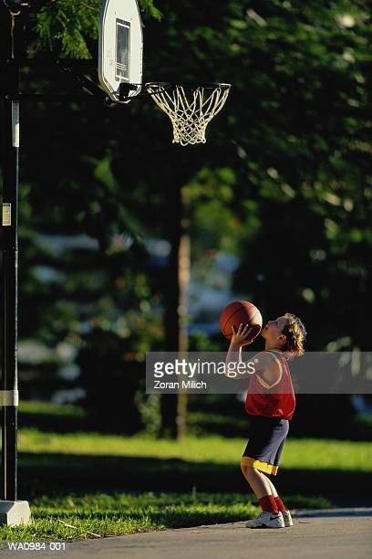 Girl (10-12) playing basketball, profile