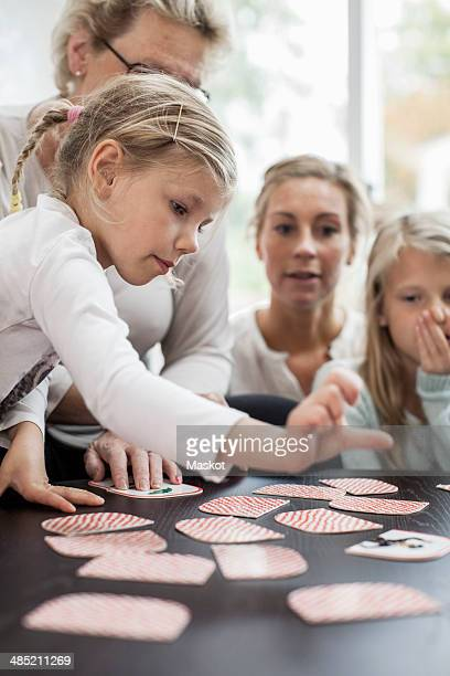 girl playing card puzzle game with family at home - family at home stock photos and pictures