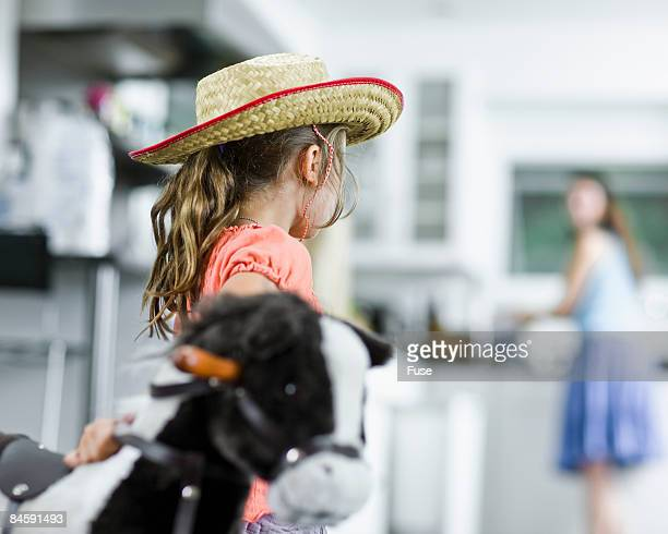 Girl Playing Cowgirl Looking Back at Mother