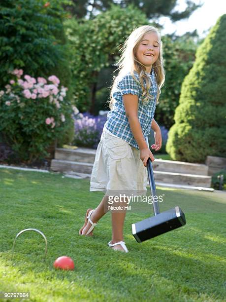 girl playing croquet on the lawn
