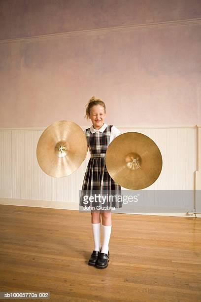 Girl (10-11) playing cymbals, eyes closed