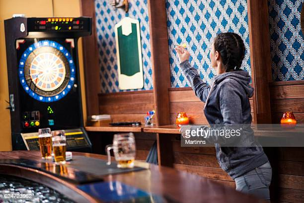 Girl playing darts at bar