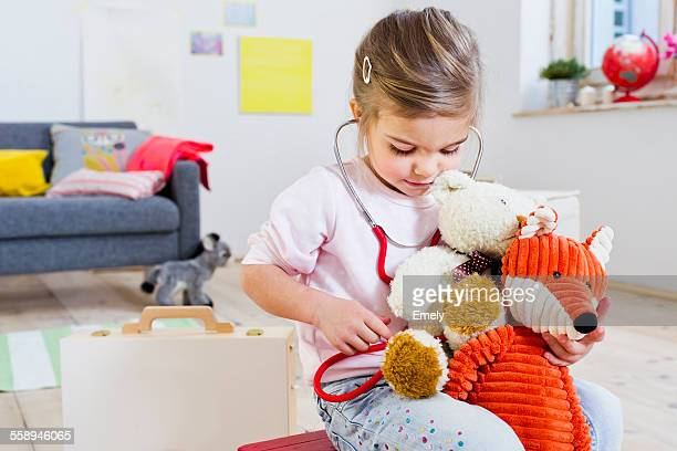 Girl playing doctor to soft toys
