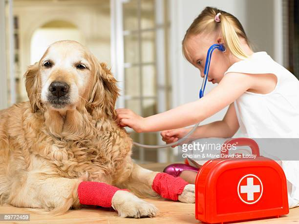 Girl playing doctor with dog
