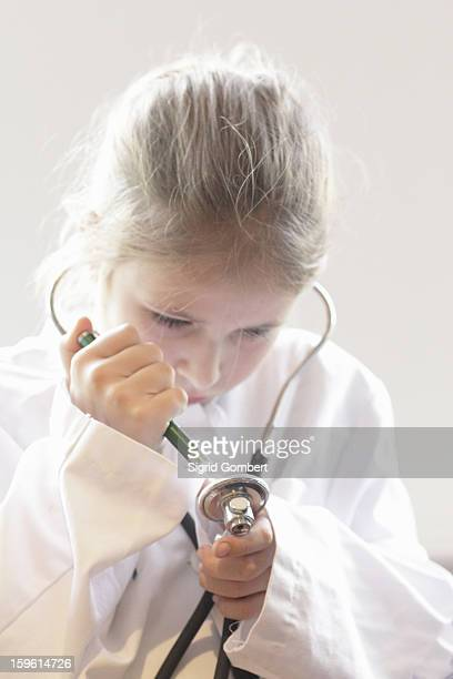 girl playing doctor with stethoscope - sigrid gombert stock pictures, royalty-free photos & images