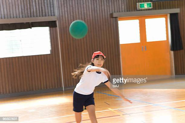 Girl playing Dodgeball in gym, blurred motion