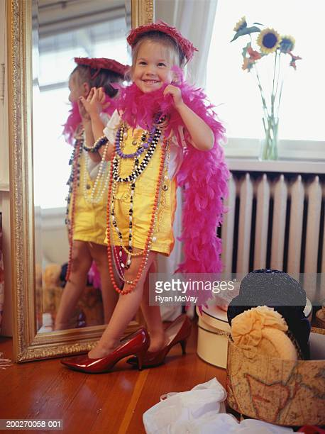 Girl (4-5) playing dress up in bedroom