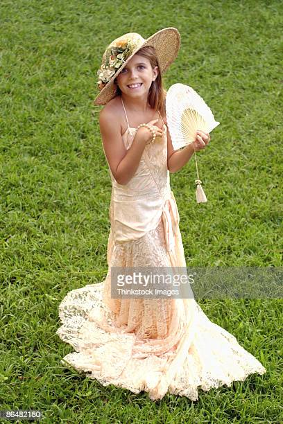 Girl playing dress up in old-fashioned gown