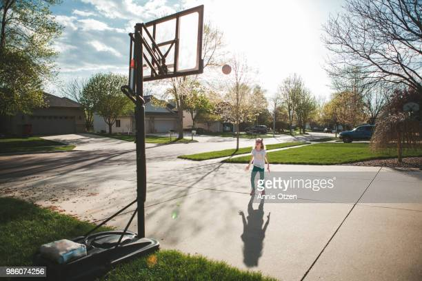 girl playing driveway basketball - driveway stock pictures, royalty-free photos & images