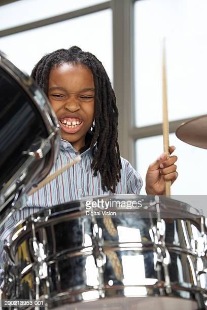 Girl (6-12) playing drums, grimacing (Focus on girl)