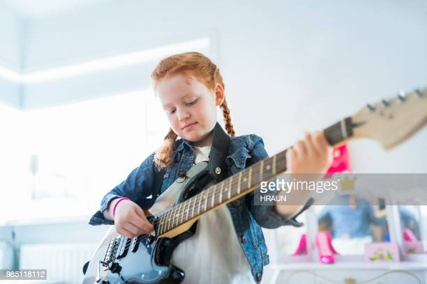 girl playing electric guitar in here room at home. - girl band stock pictures, royalty-free photos & images