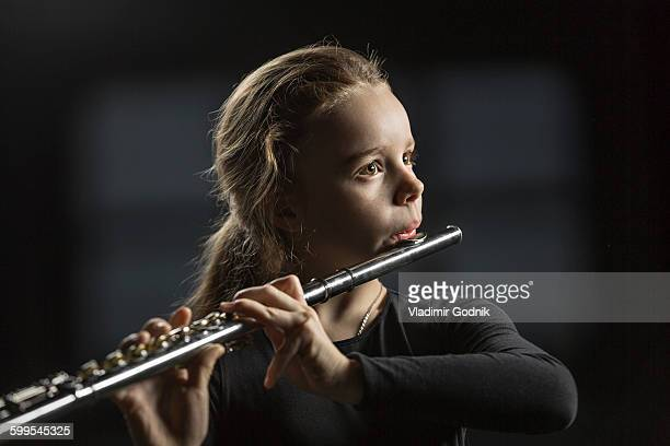 Girl playing flute against black background