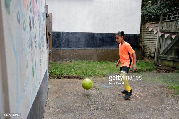 girl playing football in back garden against wall - kicking stock pictures, royalty-free photos & images