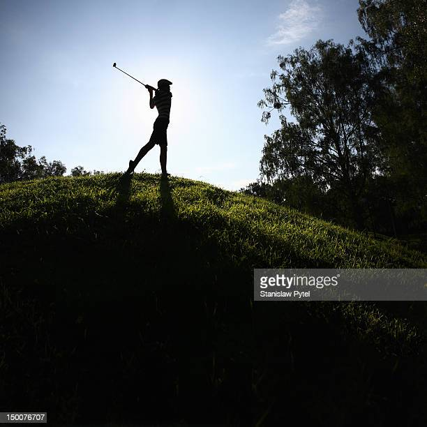 Girl playing golf on hill
