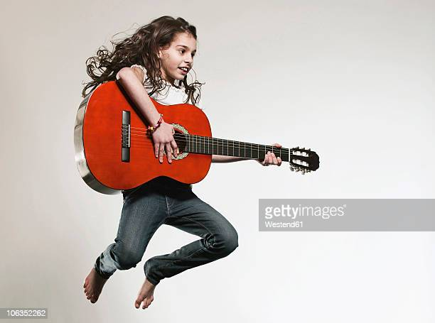 Girl (12-13) playing guitar and jumping