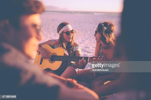 Mädchen spielt Gitarre für Ihre Freunde bei beachparty