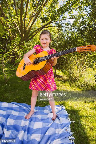 Girl playing guitar in garden