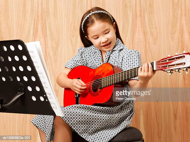 girl (6-7 years) playing guitar indoors - 6 7 years stock pictures, royalty-free photos & images