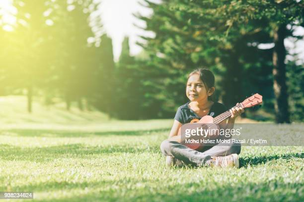 Girl Playing Guitar While Sitting On Grassy Field At Park