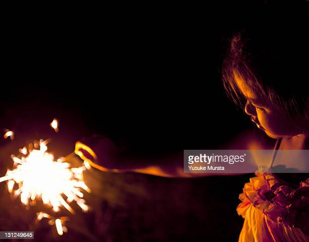 girl playing hand-held fireworks