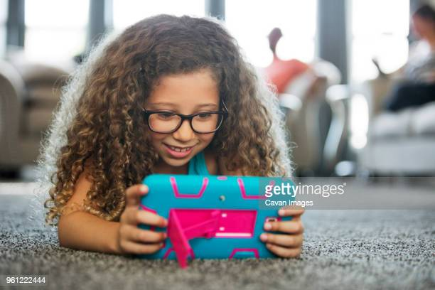 girl playing handheld video game while lying on carpet at home - handheld video game stock pictures, royalty-free photos & images