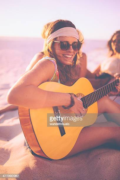 Girl playing her guitar on the beach with friends